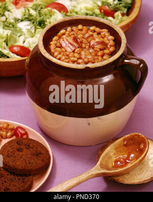 1950s COMFORT FOOD BOSTON BAKED BEANS IN BROWN CROCK WITH ROUND BROWN BREAD AND SALAD  - kf3579 FRT001 HARS OLD FASHIONED - Stock Image