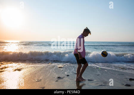 A boy with a man bun practices his football skills as the sun goes down on a Mediterranean kickingbeach - Stock Image