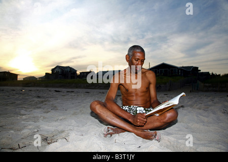 Mature African American man reading on a beach at dusk - Stock Image
