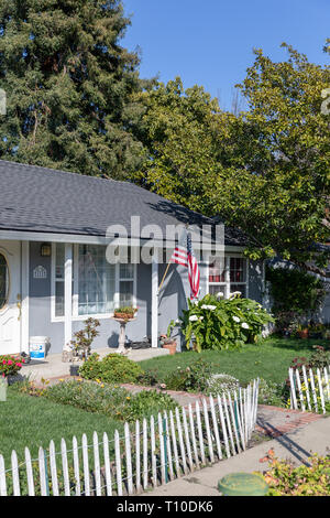 American home with flag and white wooden fence; Sunnyvale, California, USA - Stock Image