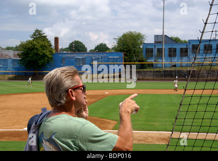 The old Durham baseball park in North Carolina, NC. Man pointing out in the athletic field while talking on the - Stock Image
