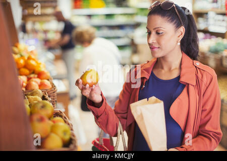 Woman shopping, examining apple in grocery store - Stock Image