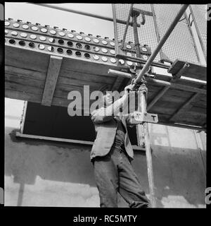 Penhill, Swindon, Swindon, Wiltshire, 1955. A man assembling scaffolding during construction of the estate. The original Laing handlist records the subject for this image as 'Personalities at Swindon'. - Stock Image