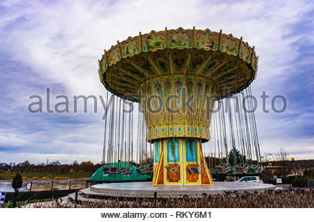 Poznan, Poland - February 10, 2019: Inactive carousel with empty seats standing close by a lake at the Malta park on a cloudy day in the winter season - Stock Image