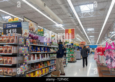 Walmart indoors with male employee stocking shelves while male customer walks down aisle. - Stock Image