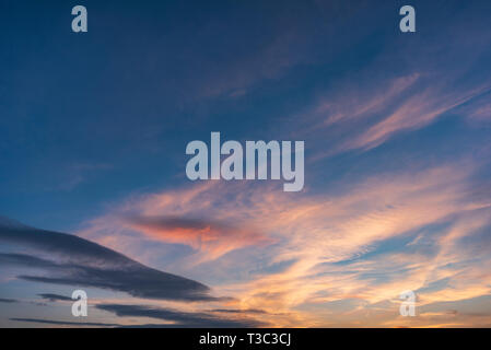 Beautiful sunset sky above clouds with dramatic light. Cabin view from airplane - Stock Image