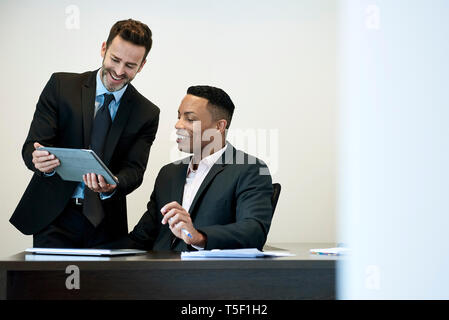 Businessmen using a digital tablet in office - Stock Image