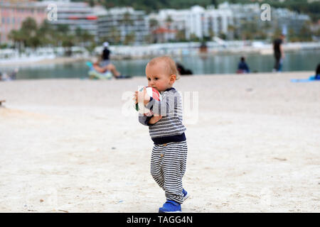 Cute Blond Baby Boy is Holding a Soccer Ball on Sand on Sea Beach in Menton, France on the French Riviera - Stock Image