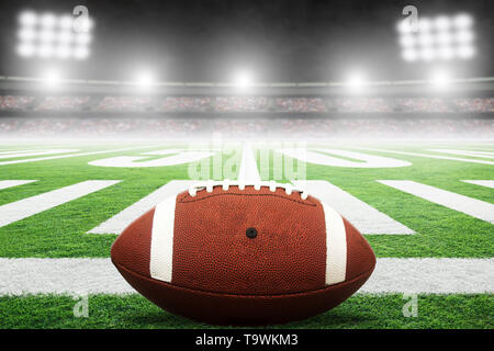 Close up of American football on stadium field with yard line markings and spotlight with blurred background and copy space. - Stock Image