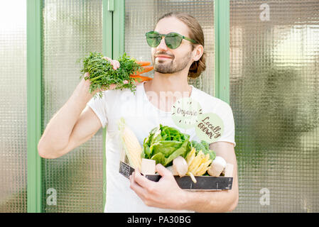 Portrait of a handsome vegetarian man standing with box full of organic vegetables outdoors - Stock Image