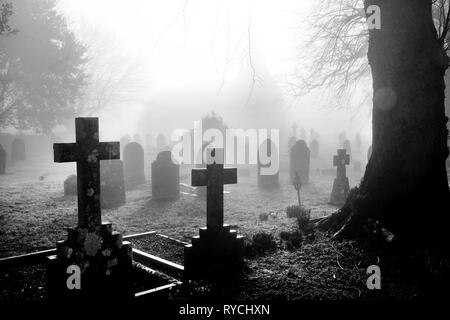 An english grave yard in the mist, in the foreground the head stones are in the shape of Christian crosses the head stones become more shrowded in mis - Stock Image