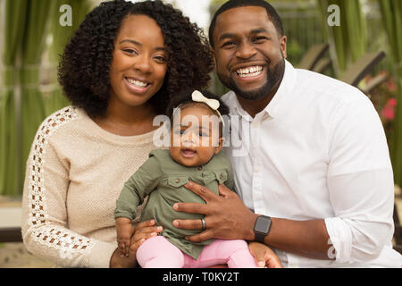 African American Family playing and laughing with their daughter. - Stock Image
