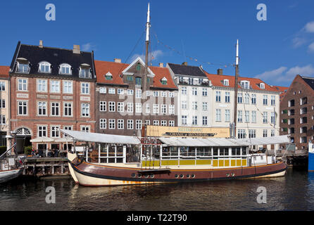 The restaurant ship Oranje af Svendborg moored in the Nyhavn Canal, Copenhagen, Denmark, in the spring sun and a blue sky. Old houses in Nyhavn. - Stock Image