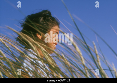8 year old Hispanic girl standing in 'tall grass' - Stock Image