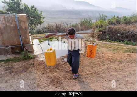 Young woman drawing water from a  well in the Taunggyi region in Shan Myanmar - Stock Image