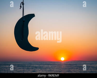 Beautifull sunrise in Greece with a model moon and the sun rising from the sea in the background. Focus on the moon. - Stock Image