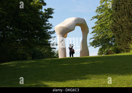 Woman Standing Under a Stone Arch Sculpture, Royal Horticultural Gardens Wisley, Woking, Surrey. - Stock Image
