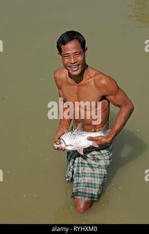 BANGLADESH Farid Pathang with a fish caught in his pond, Garo tribal minority Haluaghat, Mymensingh region photo by Sean Sprague - Stock Image