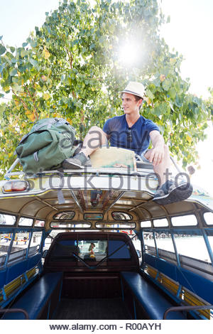 Young man sitting on tour bus roof - Stock Image