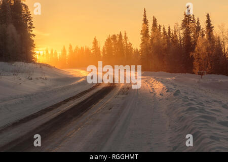 Winter landscape in direct light with road leading in to the light, fog and mist over the road, Gällivare, Swedish Lapland, Sweden - Stock Image
