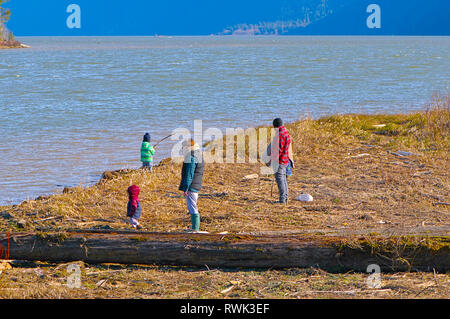 A family wearing winter clothing enjoying time at Pitt Lake on a windy day in March. Grant Narrows Regional Park, Pitt Meadows, B. C., Canada - Stock Image