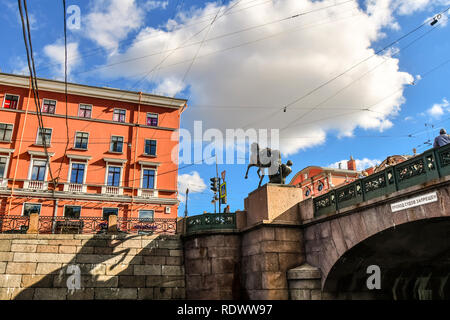 View from a canal of electrical and telephone wires crossing erratically above Anichkov Bridge and Horse Tamer sculpture in Saint Petersburg, Russia - Stock Image