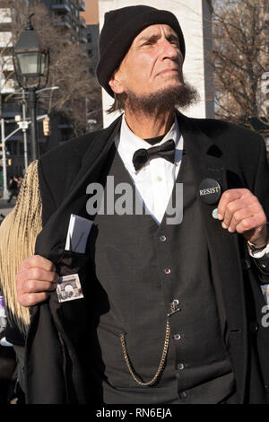 A nicely dressed older man in a suit with a resist button on his lapel and a 'fuck trump' button inside his jacket. In Washington Square Park in NYC. - Stock Image