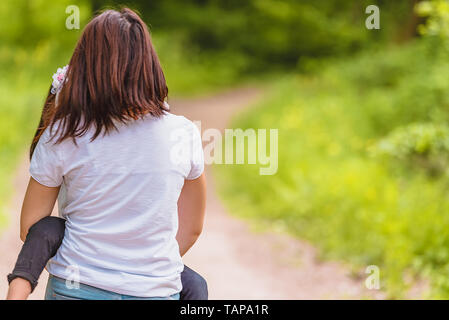 Young mom holds and hugs her little girl in forest.Happy mother and daughter moments with love and natural emotion.Photo of  mother and daughter havin - Stock Image