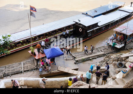 High view of tourists boats moored by jetty below steps to Pak Ou or Tham Ting Caves on Mekong River. Pak Ou, Luang Prabang province, Laos, Asia - Stock Image