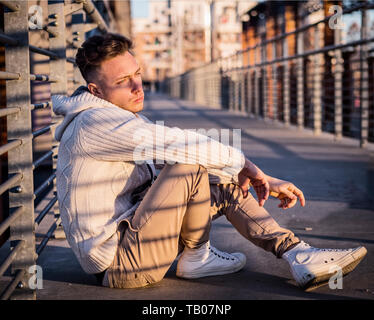 Handsome trendy young man, sitting on a sidewalk in city - Stock Image