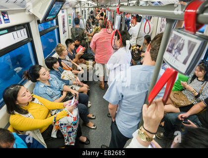 People travelling on a BTS sky train in Bangkok Thailand - Stock Image