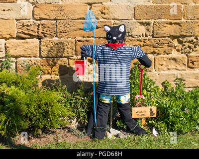 Marske North Yorkshire August 25th/ Like many Yorkshire villages Marske by the Sea has a weeklong Scarecrow Festival which started today 25th August,  many different organisations and social groups have made scarecrows an erected them around the village.  Parents and children can get a trail map to follow and view all the exhibits.  There is a prize draw at the end of the week. This cat is by the local Folk Museum  Winkies Castle in a former cobblers shop it had a cat called Winkie' Credit: Peter Jordan_NE/Alamy Live News - Stock Image