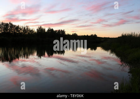 Landscape with views of pink clouds over the lake at sunset - Stock Image