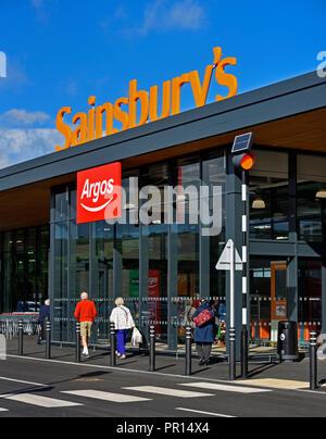 Customers approaching Sainsbury's  and Argos Supermarket. Shap Road, Kendal, Cumbria, England, United Kingdom, Europe. - Stock Image