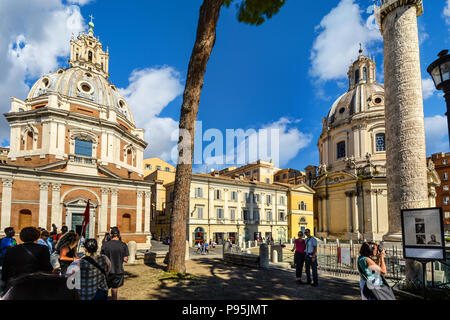 Tourists pose for a selfie as a tour group sightsees at Trajan's Column alongside the Church of the Most Holy Name of Mary in Rome, Italy - Stock Image