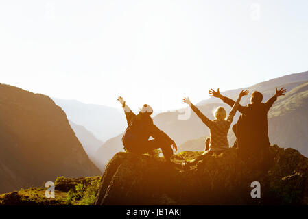 Happy friends at sunset in mountains range - Stock Image