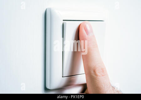 Male Finger Touching A Light Switch To Turn The Light On Or Off - Stock Image