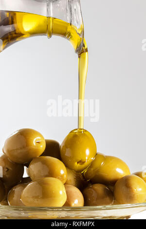 Olive Oil being poured on queen olives - Stock Image