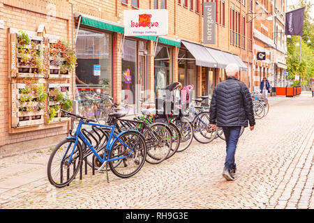 14 September 2018: Gothenburg, Sweden - A typical row of shops in the city, with bicycles parked outside. - Stock Image