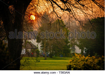Sunrise over Menlove Gardens, the early morning sun peeks above the semi detached  suburban houses in Allerton, Liverpool L18 England Merseyside UK - Stock Image