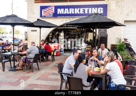 Cartagena Colombia El Laguito beach cafe restaurant tables umbrellas Hispanic resident residents man woman - Stock Image