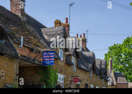 The Althorp Coaching Inn (or Fox and Hounds as it was previously known), a 16th century thatched and stone-built inn Great Brington, UK - Stock Image