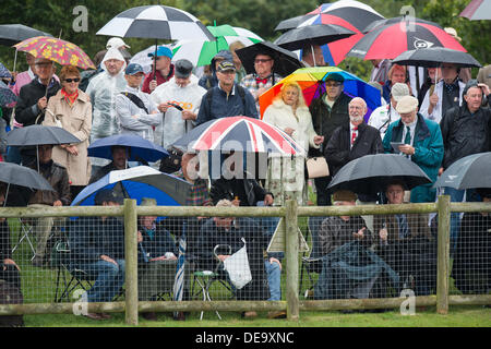 Chichester, West Sussex, UK. 13th Sep, 2013. Goodwood Revival. Goodwood Racing Circuit, West Sussex - Friday 13th September. Spectators shelter under umbrellas during a period of rain. © MeonStock/Alamy Live News - Stock Image