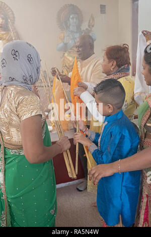 Devout Hindu worshippers tie victory flags to bamboo poles at a Shakti Temple in Jamaica, Queens, New York City. - Stock Image