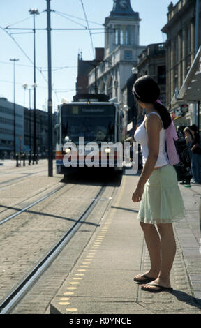 teenage girl university student waiting for oncoming tram, Sheffield, England - Stock Image