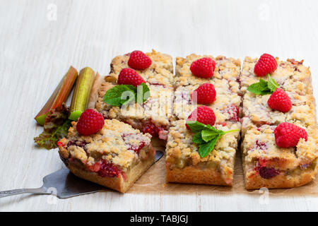 Homemade  rhubarb tart with raspberry on white wooden table - Stock Image