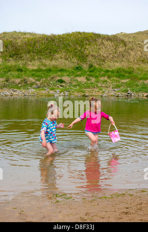 2 sisters aged 3 and 4 years old, gathering water at the beach. - Stock Image