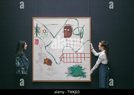 London, UK. 21st June, 2019. Sotheby's technicians with 'Big Snow, 1984', Acrylic and oilstick on canvas by Jean-Michel Basquiat. Estimate: £3,500,000-4,500,000 at the Sotheby's Contemporary Art Auction preview for the Evening sale on 26 June Credit: amer ghazzal/Alamy Live News - Stock Image