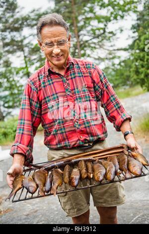 Senior man with smoked fish - Stock Image