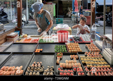 Thailand street food stall selling sushi and with child helping mother - Stock Image